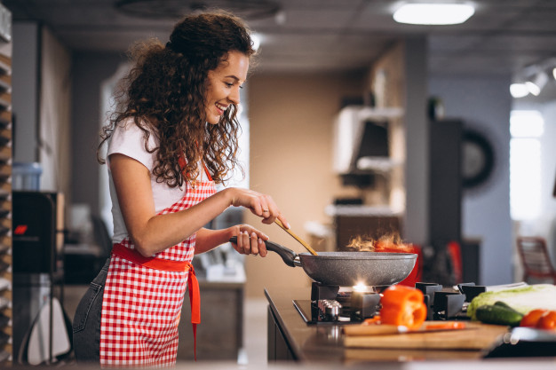 woman-chef-cooking-vegetables-pan_1303-22287